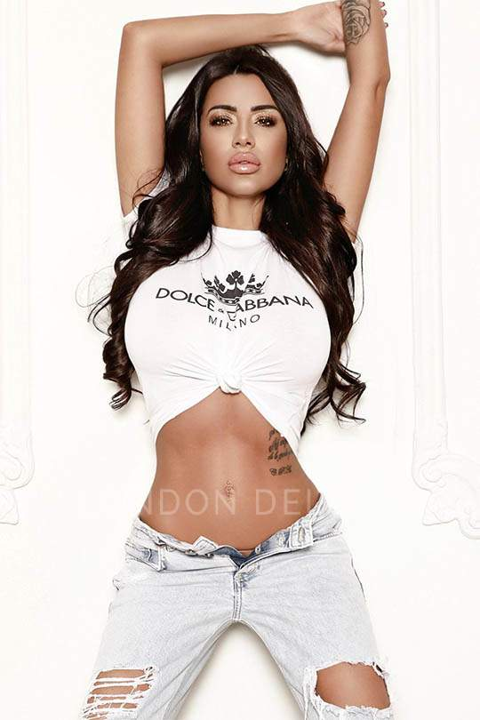 Kim posing in white dolce and gabbana top and ripped denim jeans