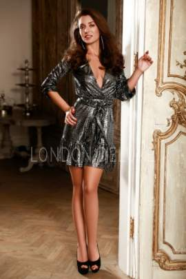 Sandra in a glistening gray dress posing in front of a door